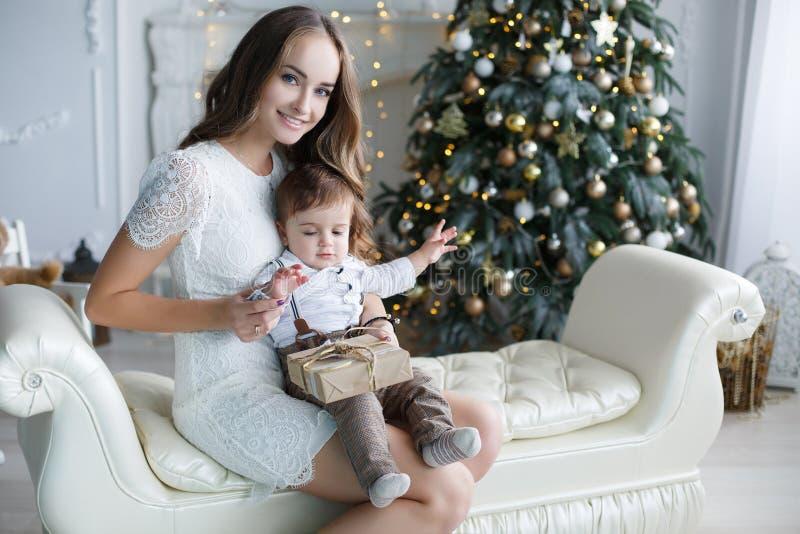 Moeder en jonge zoon thuis dichtbij Kerstboom stock foto's