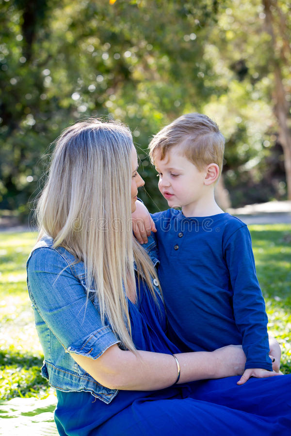 Moeder en jonge zoonszitting die dicht samen in openlucht I spreken royalty-vrije stock fotografie