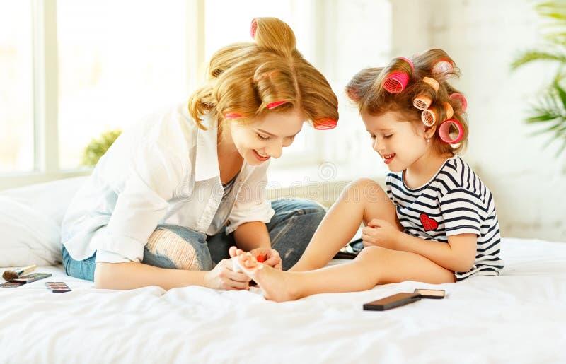 Moeder en kind de dochter in haarkrulspelden schildert spijkers, maakt pedi stock fotografie