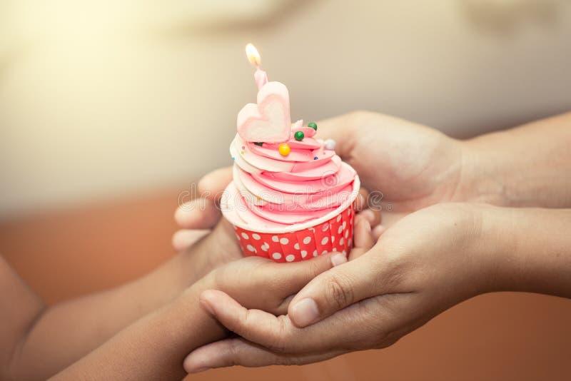 Moeder en kind de verjaardag van de handholding cupcake royalty-vrije stock fotografie