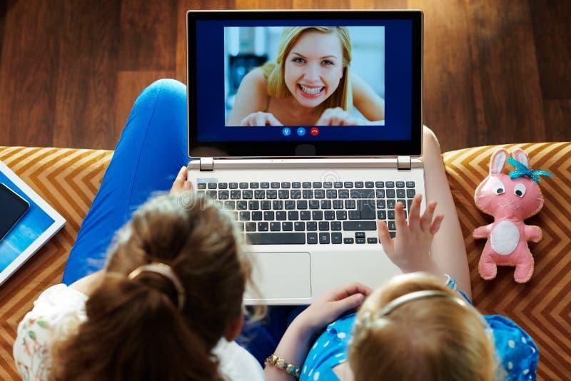 Moeder en kind die computer voor videogesprek op laptop met behulp van stock fotografie
