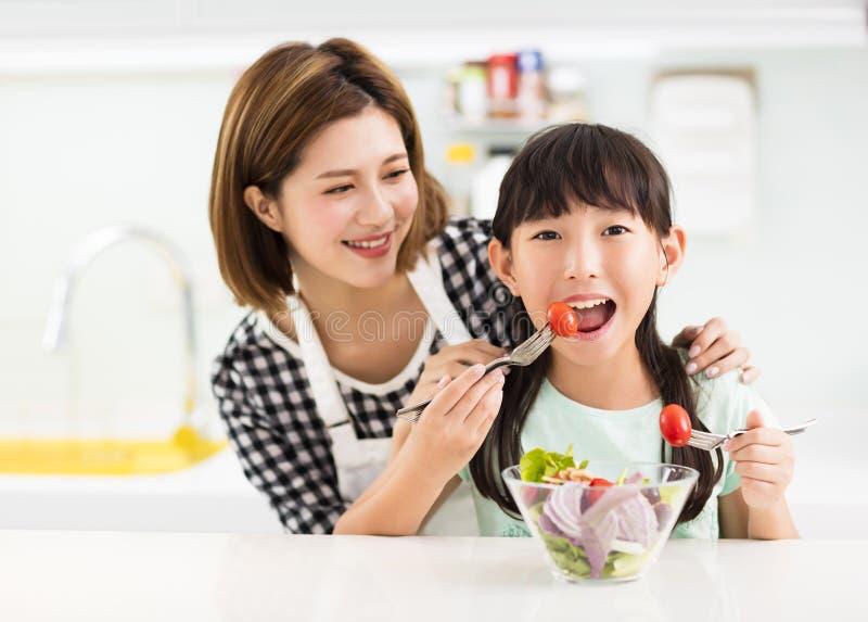 Moeder en kind die in keuken salade eten stock foto