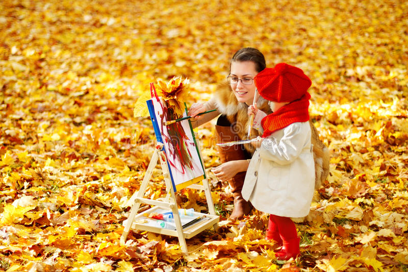 Moeder en kind die op schildersezel in de herfstpark trekken Creatieve jonge geitjes royalty-vrije stock foto