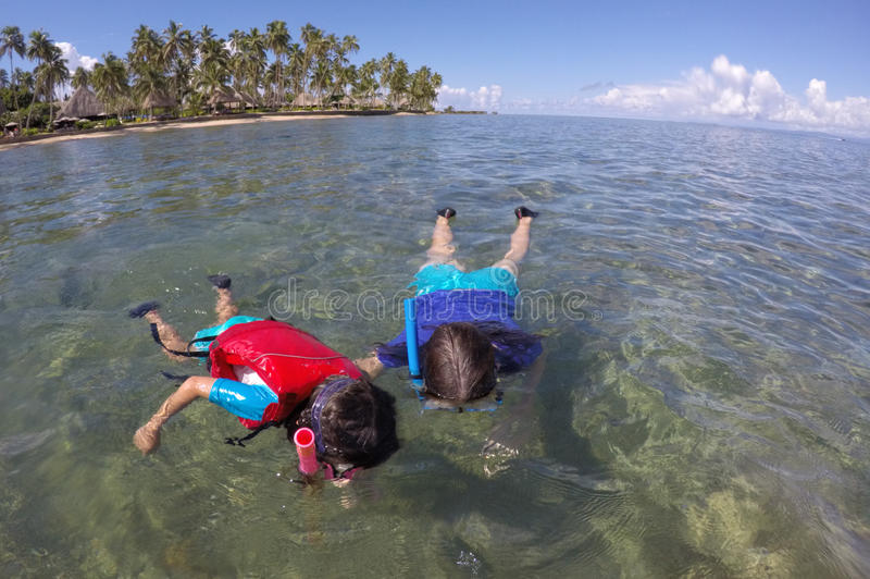 Moeder en kind die over een koraalrif Fiji snorkelen stock foto's