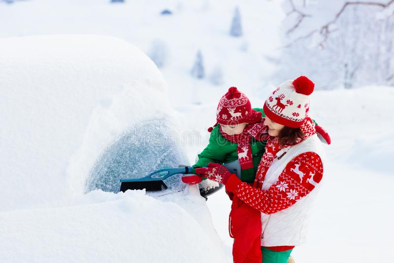 Moeder en kind die en sneeuw borstelen scheppen van auto na onweer Ouder en jong geitje met de winterborstel en de familieauto va stock afbeeldingen