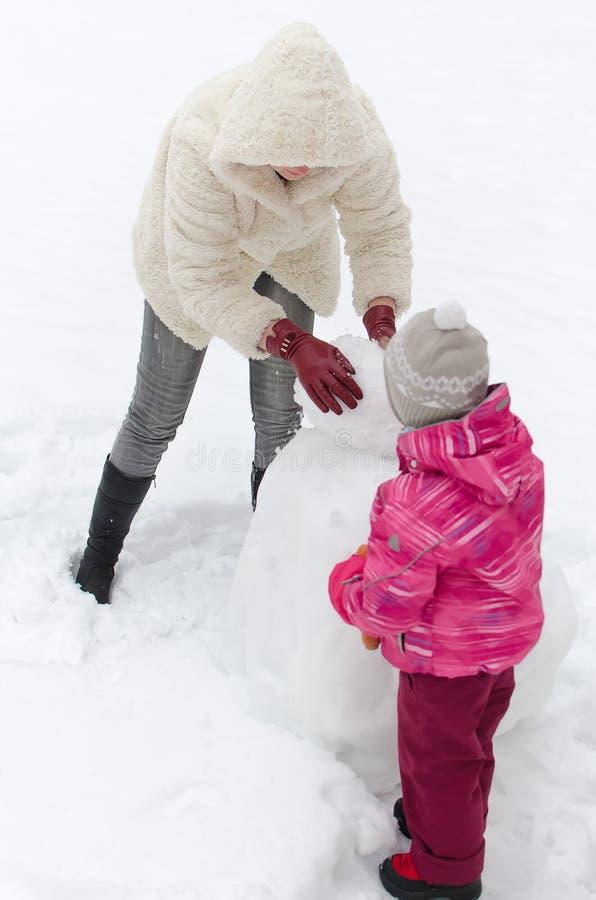 Moeder en kind die sneeuwman maken stock fotografie