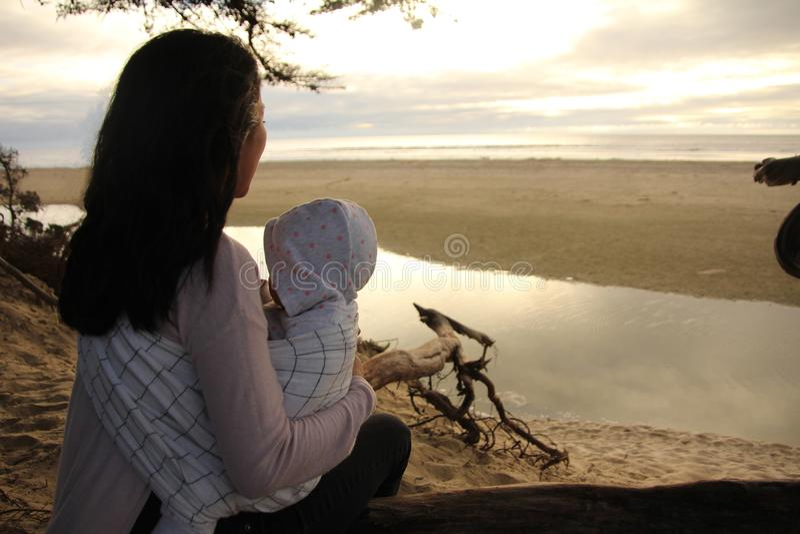 Moeder en kind die van een strandzonsondergang genieten royalty-vrije stock fotografie