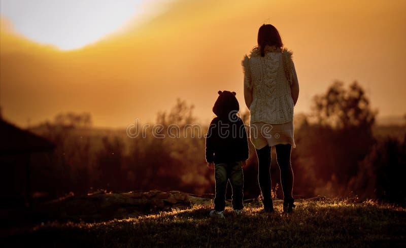 Moeder en kind die zonsondergang bekijken royalty-vrije stock fotografie