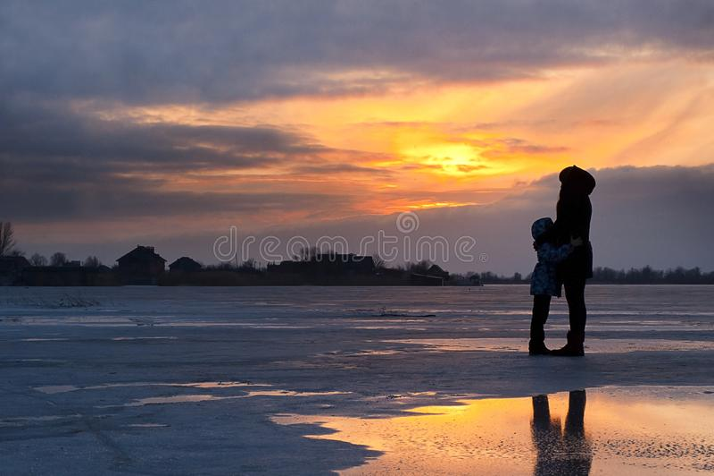 Moeder en kind door bevroren meer bij zonsondergang