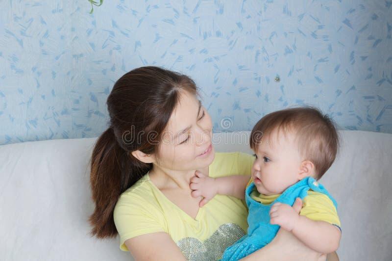 Moeder en kind, gelukkige glimlachende vrouw met weinig baby, multinationale familie met Aziatisch mamma en dochter stock foto's