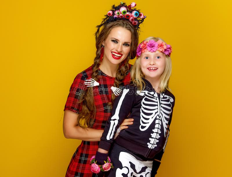 Moeder en kind in Halloween-kostuum op gele achtergrond stock afbeelding