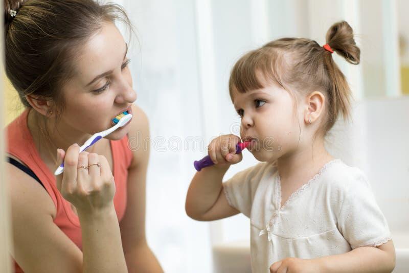 Moeder en kind het borstelen tanden samen in de ochtend - tandzorgconcept stock foto's