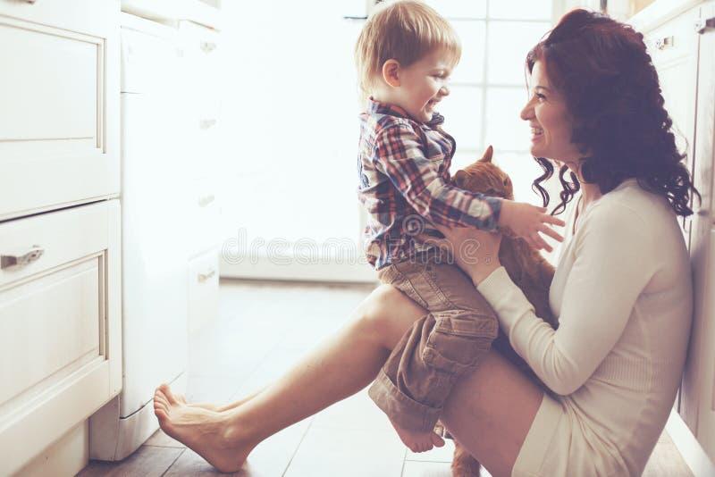 Moeder en kind het spelen met kat stock fotografie