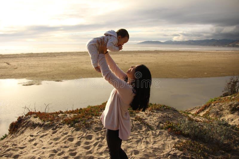 Moeder en kind het spelen op een strand stock afbeeldingen