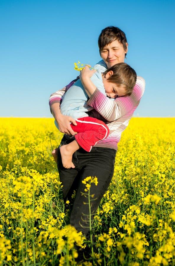 Moeder en kind op een raapzaadgebied stock fotografie