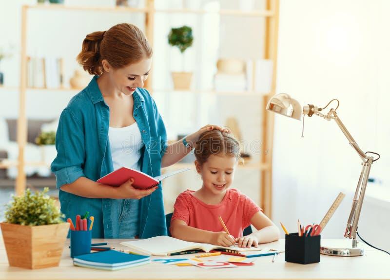 Moeder en kinddochter die en thuiswerk doen die schrijven lezen royalty-vrije stock foto's