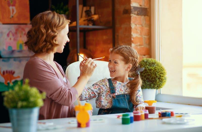 Moeder en kinddochter het schilderen trekt in creativiteit in kleuterschool stock foto