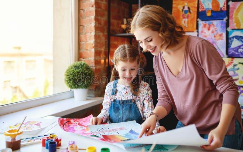 Moeder en kinddochter het schilderen trekt in creativiteit in kleuterschool stock foto's