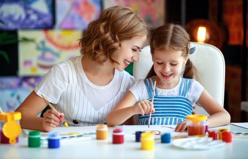 Moeder en kinddochter het schilderen trekt in creativiteit in kleuterschool stock afbeeldingen