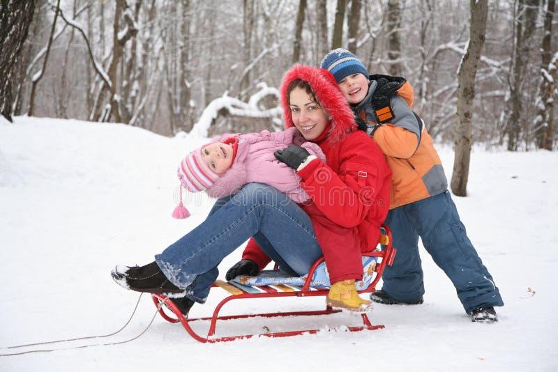 Moeder en kinderen in bos bij de winter stock foto