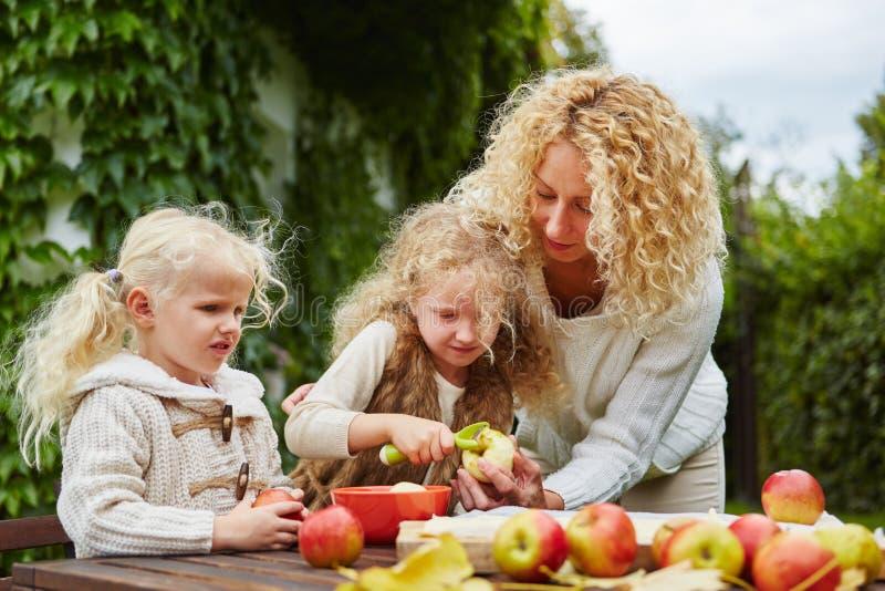 Moeder en kinderen die appelen pellen stock foto