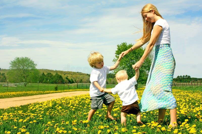 Moeder en Kinderen die buiten spelen stock fotografie