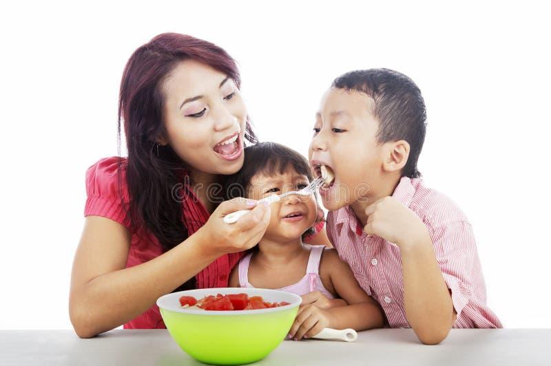 Moeder en kinderen die fruitsalade eten royalty-vrije stock afbeelding