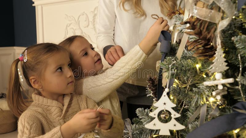 Moeder en kinderen die Kerstmisboom in mooie familiewoonkamer verfraaien met open haard royalty-vrije stock fotografie