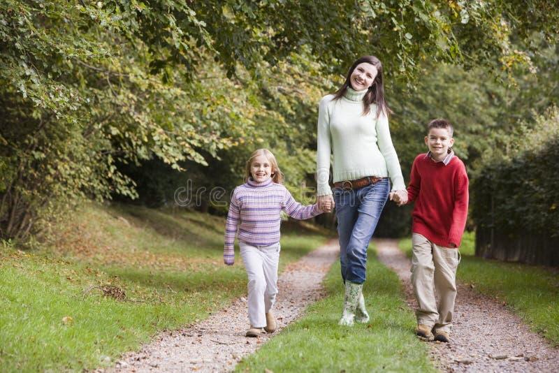 Moeder en kinderen die langs bosweg lopen royalty-vrije stock fotografie