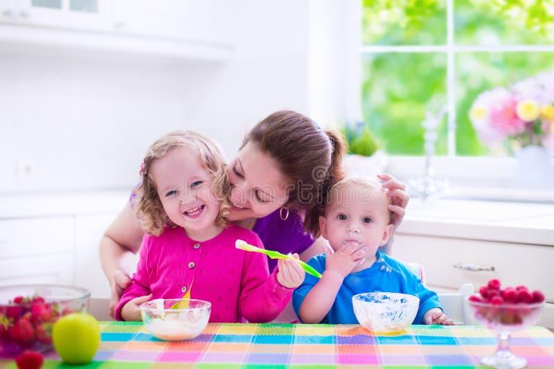 Moeder en kinderen die ontbijt hebben royalty-vrije stock afbeeldingen