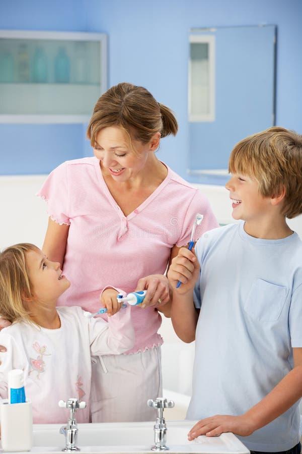 Moeder en kinderen die tanden in badkamers schoonmaken royalty-vrije stock foto's