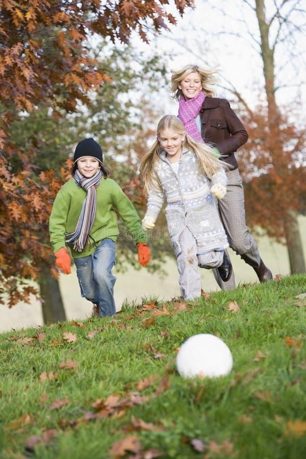 Moeder en kinderen die voetbal in tuin spelen royalty-vrije stock foto's