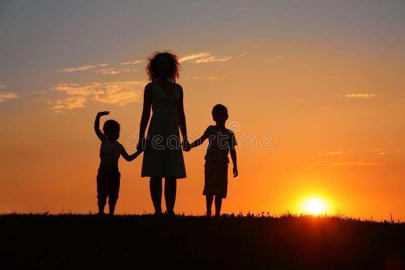 Moeder en kinderen op zonsondergangsilhouet stock foto's