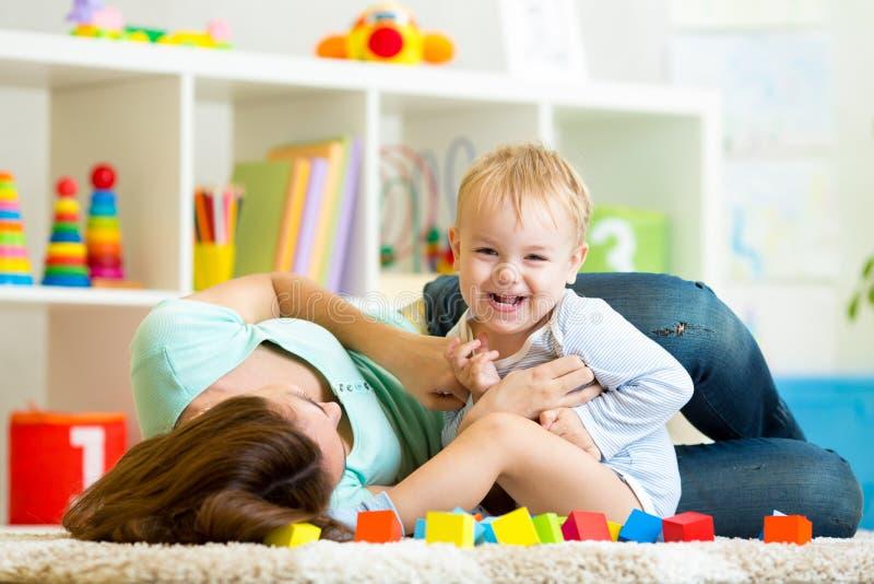 Moeder en kindjongensspel samen binnen stock afbeeldingen