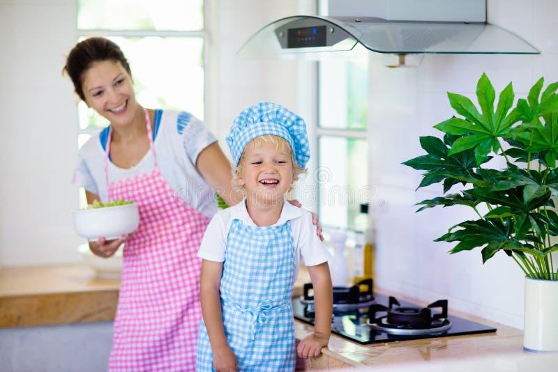Moeder en kindkok Mamma en jong geitjekok in keuken stock fotografie