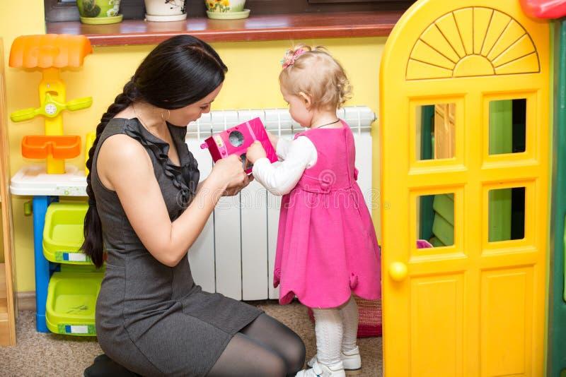 Moeder en kindmeisje het spelen in kleuterschool royalty-vrije stock foto's
