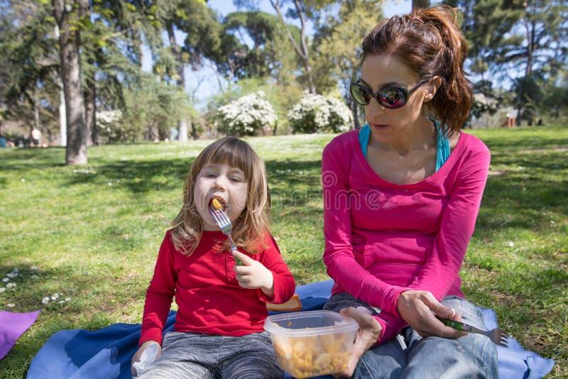 Moeder en kindzitting in park die deegwaren eten royalty-vrije stock afbeeldingen