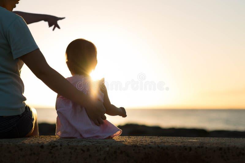 Moeder en kindzitting samen op het strand, die op de mooie zonsondergang letten stock foto