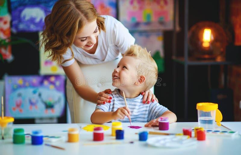 Moeder en kindzoon het schilderen trekt in creativiteit in kleuterschool royalty-vrije stock fotografie