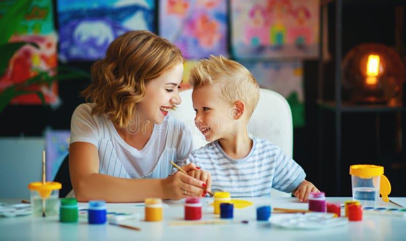 Moeder en kindzoon het schilderen trekt in creativiteit in kleuterschool royalty-vrije stock foto's