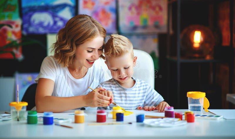 Moeder en kindzoon het schilderen trekt in creativiteit in kleuterschool moeder en kindzoon het schilderen trekt is bezig geweest stock foto's