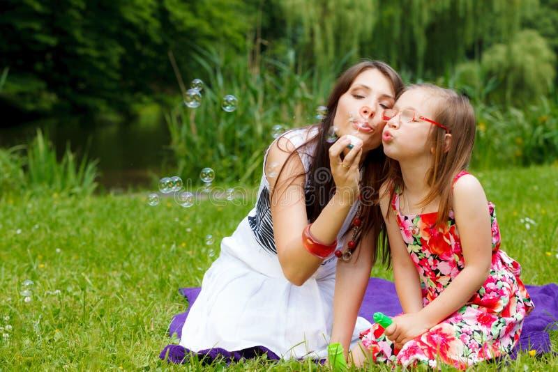Moeder en meisje blazende zeepbels in park royalty-vrije stock afbeelding