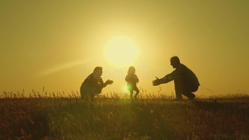 Moeder en papaspel met hun dochter in de zon de gelukkige baby gaat van papa naar mamma jonge familie op het gebied met a royalty-vrije stock foto