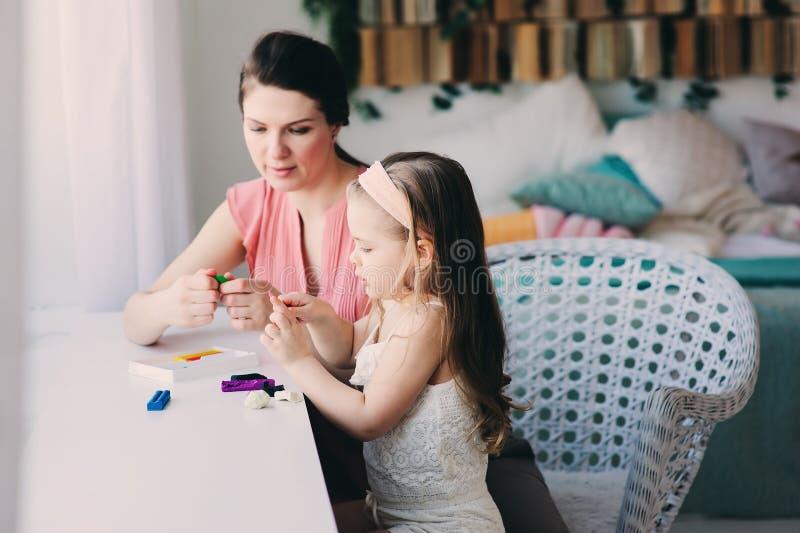 Moeder en peuterdochter het spelen met plasticine of plasticine thuis stock afbeelding