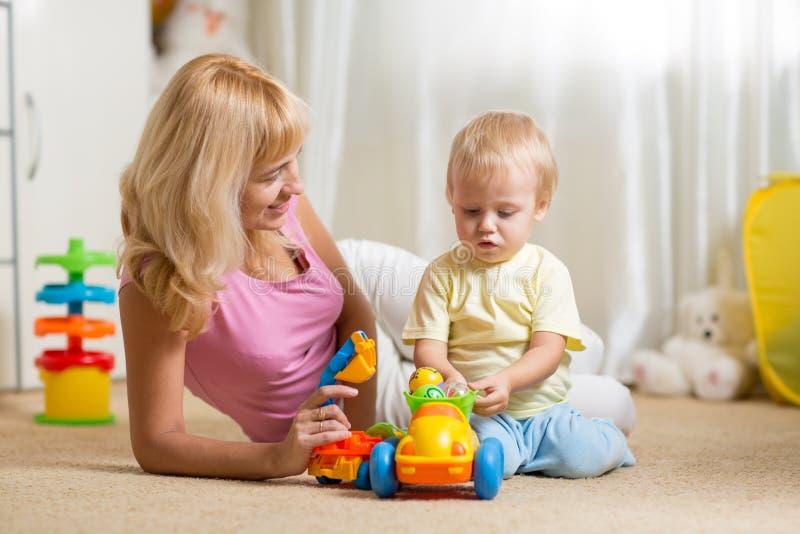 Moeder en peuterzoonsspel met stuk speelgoed auto  stock afbeelding