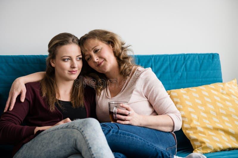 Moeder en tienerdochter die op bank thuis koesteren royalty-vrije stock fotografie