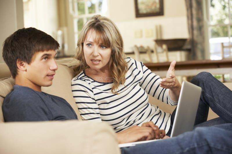 Moeder en Tienerzoon die op Sofa At Home debatteren royalty-vrije stock afbeeldingen