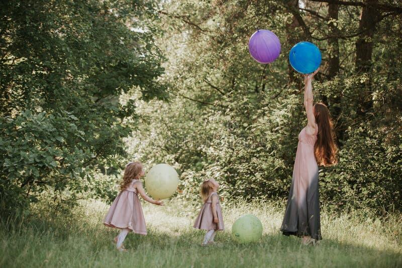 Moeder en twee dochters die handen het omcirkelen houden familie tijd samen Grappige tijd Meisjes met Ballons Zachte nadruk stock afbeelding