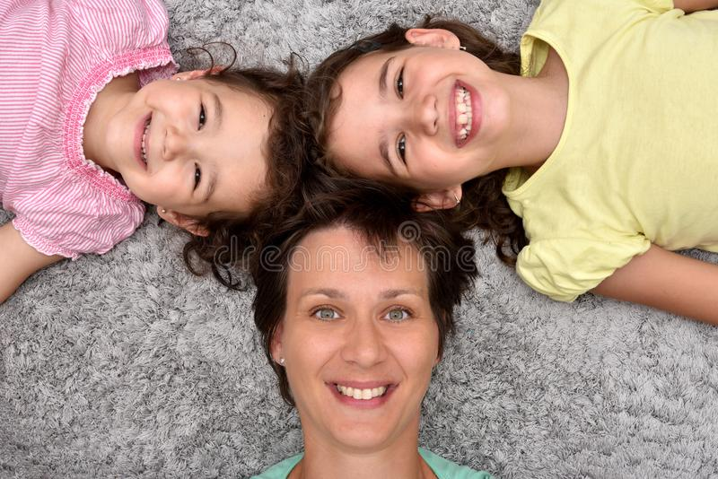 Moeder en twee dochters die op het tapijt liggen royalty-vrije stock afbeelding