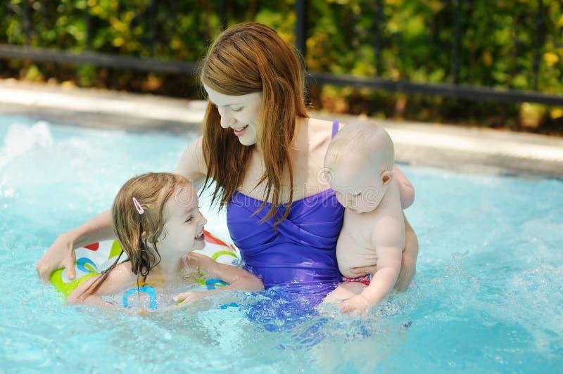 Moeder en twee dochters die in pool zwemmen stock afbeelding